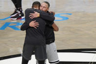 Golden State Warriors guard Stephen Curry, right, embraces Brooklyn Nets forward Kevin Durant during pregame warmups before the start of an opening night NBA basketball game between the Warriors and the Nets, Tuesday, Dec. 22, 2020, in New York. (AP Photo/Kathy Willens)