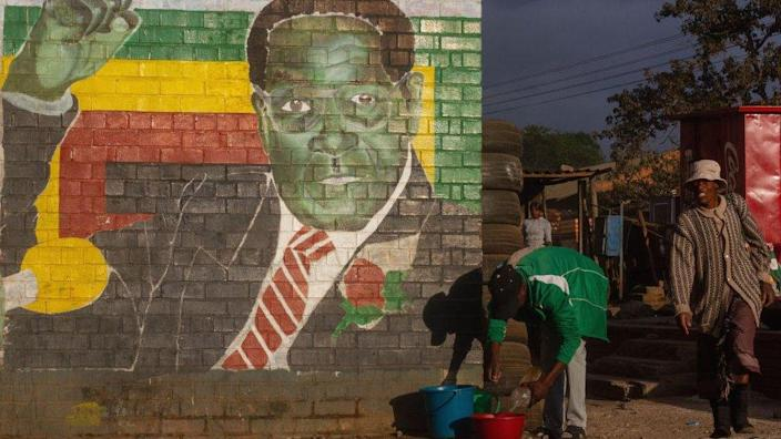 People in Harare Mbarre, a mural of the late President Robert Mugabe of Zimbabwe-2019
