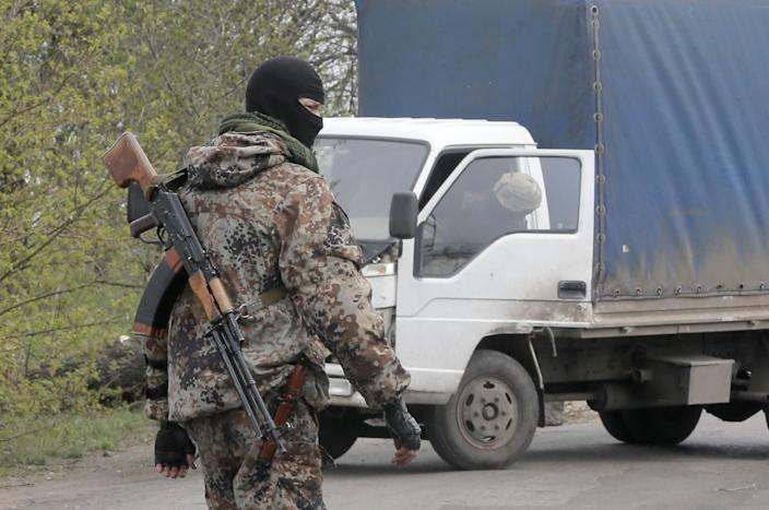 A pro-Russian gunman controls a road after a night fight at the check point which is under the control of pro-Russian activists in the village of Bulbasika near Slovyansk, Ukraine, Sunday, April 20, 2014. At least one person was dead. Pro-Russian insurgents defiantly refused to surrender their weapons or give up government buildings in eastern Ukraine, despite a diplomatic accord reached in Geneva and overtures from the government in Kiev. (AP Photo/Efrem Lukatsky)