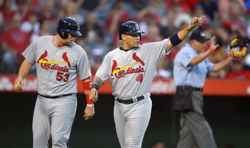 St. Louis Cardinals' Yadier Molina, center, gestures toward Daniel Descalso as Matt Adams watches, after they scored on Descalso's double during the second inning of a baseball game against the Los Angeles Angels, Wednesday, July 3, 2013, in Anaheim, Calif. (AP Photo/Mark J. Terrill)