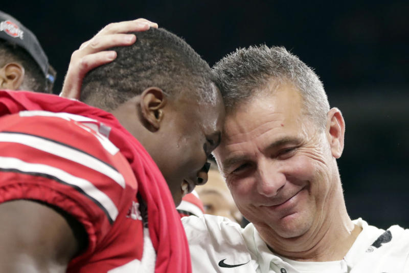 Ohio State head coach Urban Meyer and wide receiver Terry McLaurin left celebrate early after defeating Northwestern 45-24 in the Big Ten championship NCAA college football game in Indianapolis. Meyer the highly