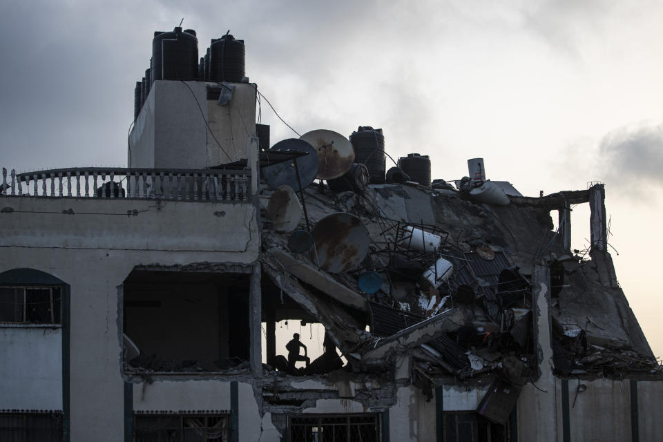 A Palestinian searches for survivors under the rubble of a destroyed rooftop of a residential building which was hit by Israeli missile strikes, at the Shati refugee camp in Gaza City, early Tuesday, May. 11, 2021. (AP Photo/Khalil Hamra)