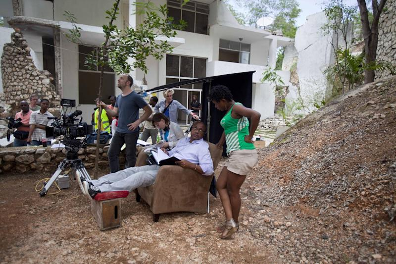 """Haitian film Director Raoul Peck, sitting center, speaks with Haitian actress Lovely Kermonde Fifi on the set of the film """"Murder in Pacot"""" at a home that was damaged in the 2010 earthquake in Port-au-Prince, Haiti, Friday, April 11, 2014. Peck, whose past films include """"The Man by the Shore"""" about dictatorship-era Haiti, the Rwanda genocide drama """"Sometimes in April"""" and """"Lumumba: Death of a Prophet,"""" said he came up with the idea for the film while shooting """"Fatal Assistance,"""" a documentary that takes a harsh look at Haiti's reconstruction effort. (AP Photo/Dieu Nalio Chery)"""