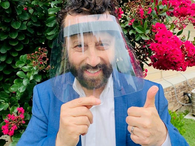 Yakov Smirnoff, smiling behind a face shield, gives a thumbs up