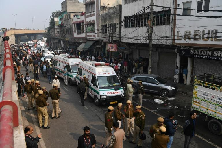 Police personnel and ambulances line up to aid victims of the deadly blaze that ripped through a four-storey bag factory in New Delhi (AFP Photo/Sajjad  HUSSAIN)