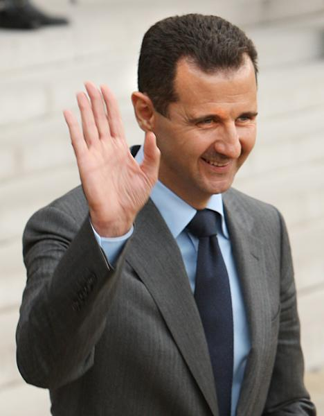 FILE - In this Friday Nov. 13, 2009 file photo, Syrian President Bashar Assad waves a goodbye as he leaves the Elysee Palace following his meeting with his French counterpart Nicolas Sarkozy, in Paris. Arab identity is back on the right track after the fall from power of Egypt's Muslim Brotherhood, which had used religion for its own political gain, Assad said in remarks published Thursday. (AP Photo/Remy de la Mauviniere, File)