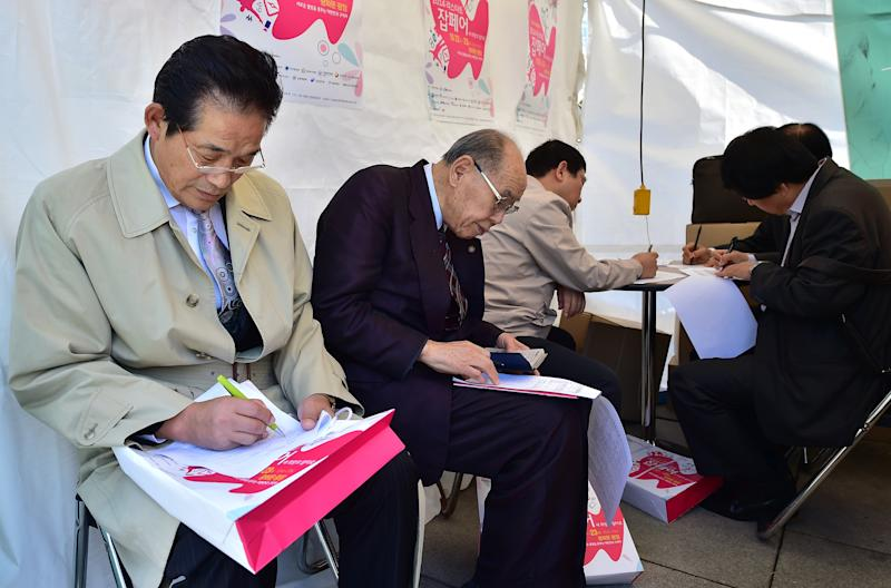 South Korean elderly men fill out application forms for employment at a job fair in Seoul, on October 22, 2014 (AFP Photo/Jung Yeon-Je)