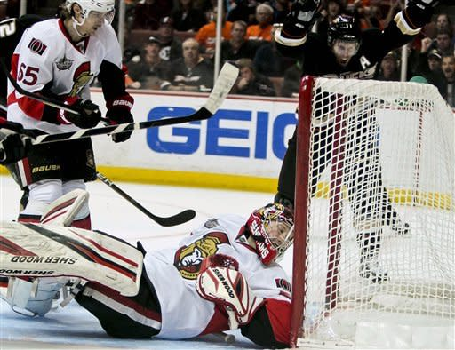 Ottawa Senators goalie Craig Anderson, bottom, and Senators defenseman Erik Karlsson, left, from Sweden, look at the puck in the back of the net off a goal by Anaheim Ducks defenseman Lubomir Visnovsky (not shown) as Ducks center Saku Koivu, right, from Finland, celebrates during the second period of an NHL hockey game on Saturday, Jan. 21, 2012, in Anaheim, Calif. (AP Photo/Bret Hartman)