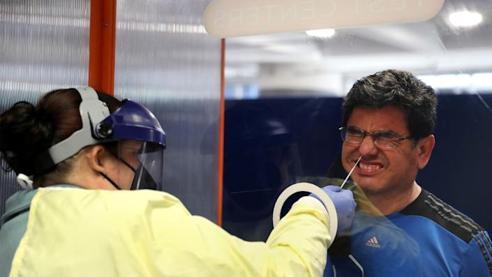Luis Mostacero receives a Covid-19 test from testing technician Jamie Kunzer at Doctors Test Centers at Chicago's O'Hare International Airport on Thursday, May 20, 2021. (Chris Sweda/Chicago Tribune/Tribune News Service via Getty Images)