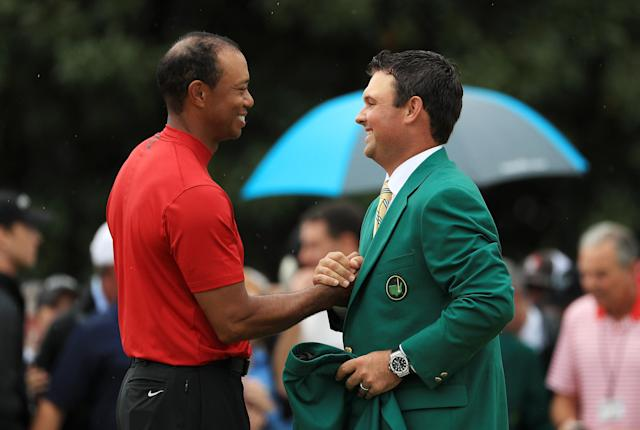 Tiger Woods (L) of the United States is shakes hands with Masters champion Patrick Reed (R) during the Green Jacket Ceremony after winning the Masters at Augusta National Golf Club on April 14, 2019 in Augusta, Georgia. (Photo by Mike Ehrmann/Getty Images)