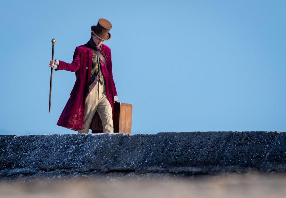 """<p>The <b>Wonka</b> costume department landed on a knee-length velvet coat in a dark magenta color that's visually similar to the one worn by <a class=""""link rapid-noclick-resp"""" href=""""https://www.popsugar.com/Johnny-Depp"""" rel=""""nofollow noopener"""" target=""""_blank"""" data-ylk=""""slk:Johnny Depp"""">Johnny Depp</a>. If you zoom in on the right lapel and lower left corner, you'll see some intricate floral embroidery that was absent from the past two films.</p>"""