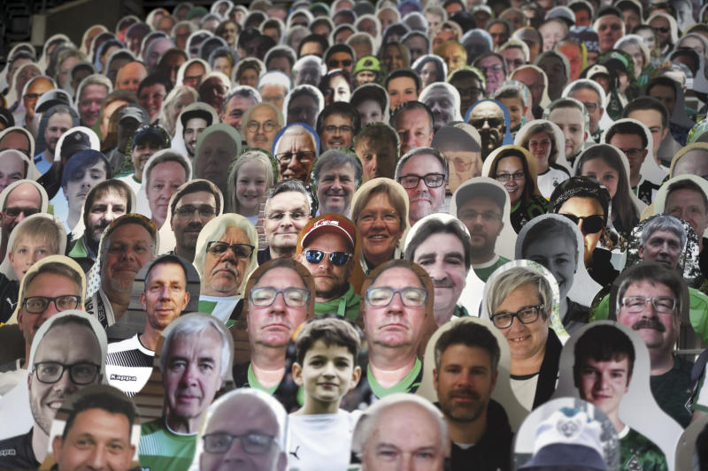 Cardboard pictures of fans are placed in the stands prior to the German Bundesliga soccer match between Borussia Moenchengladbach and Leverkusen, in Moenchengladbach, Germany, Saturday, May 23, 2020. (Ina Fassbender Pool Photo via AP)