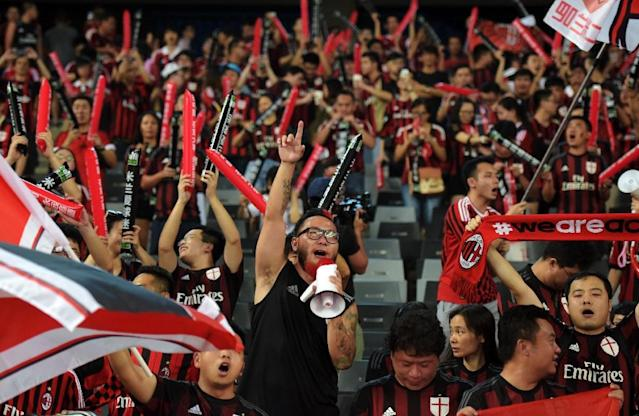 AC Milan supporter Liu Shu (C) cheers for his team ahead of the International Champions Cup match between AC Milan and Inter Milan in Shenzhen on July 25, 2015 (AFP Photo/Johannes Eisele)