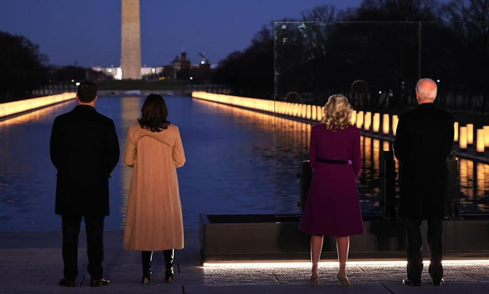 Kamala Harris, second from left, wears a camel coat featuring a water-like design at a memorial for victims of the coronavirus pandemic at the Lincoln Memorial on 19 January.