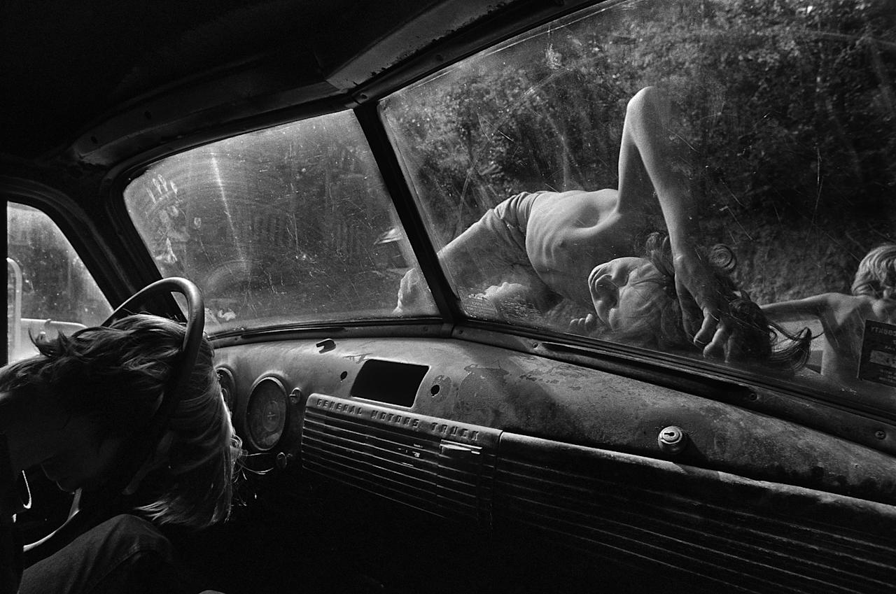 <p>Boys sleep on the hood of a pickup truck on a hot summer day in Stillhouse Hollow, Tenn., 1986. (© Eugene Richards) </p>