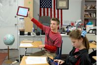 <p>A Texas high school student holds up his school-issued iPad to make a point during geography class.</p>