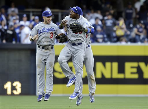 Los Angeles Dodgers outfielders Yasiel Puig, center, Skip Schumaker, let, and Andre Ethier, back, celebrate the Dodgers' 6-1 victory over the San Diego Padres in a baseball game in San Diego, Saturday, June 22, 2013. (AP Photo/Lenny Ignelzi)