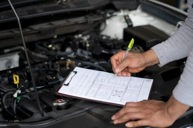 Auto mechanic (or technician) checking car engine at the garage