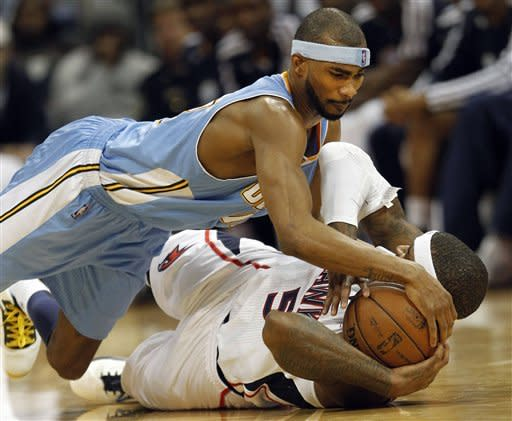 Denver Nuggets small forward Corey Brewer, top, and Atlanta Hawks small forward Josh Smith (5) scramble for a loose ball during the second half of an NBA basketball game on Wednesday, Dec. 5, 2012, in Atlanta. (AP Photo/John Bazemore)