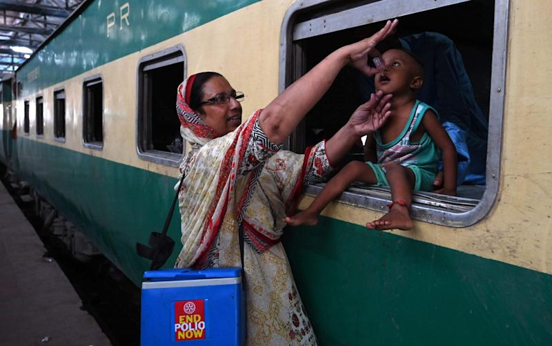 A Pakistani health worker administers polio drops to a child at a railway station during a polio vaccination campaign in Lahore last August - ALI/AFP/Getty Images