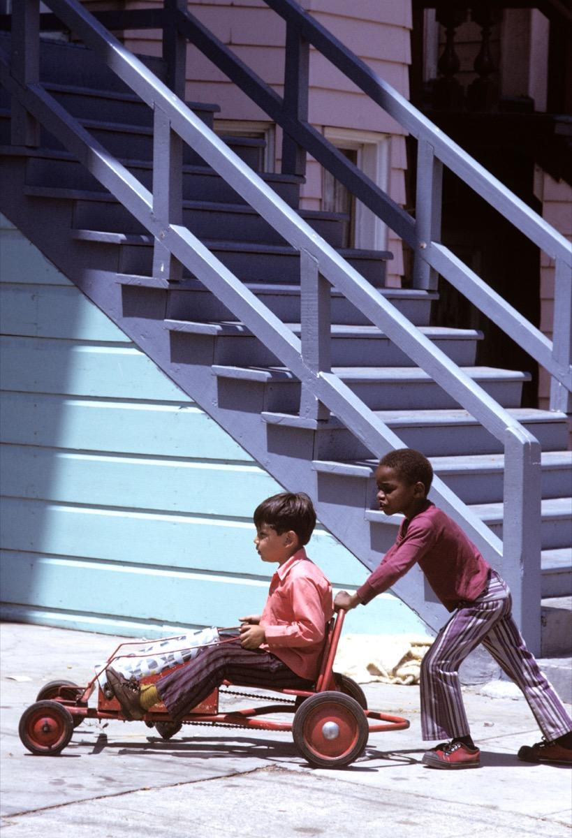 A black boy and Hispanic boy play with homemade go cart wagon in the inner city mission district of San Francisco in 1960s/70s