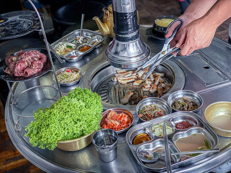 A restaurant server assisting customer with the grilling in a korean BBQ restaurant setup with various side dishes (Banchan)