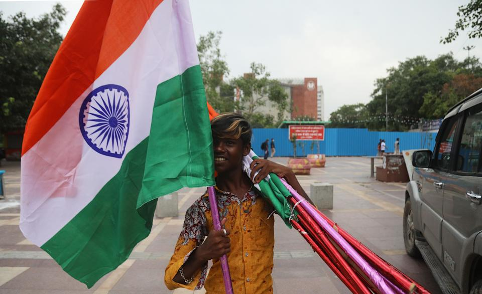 NEW DELHI, INDIA - 2020/08/14: A boy sells Tricolour flags on the eve of Independence Day at Connaught Place. Indian Prime Minister Narendra Modi will deliver his 7th Independence day speech from the rampart of Red fort on Saturday, an address that comes amid the coronavirus pandemic, a border standoff with China and his government's achievements. (Photo by Naveen Sharma/SOPA Images/LightRocket via Getty Images)