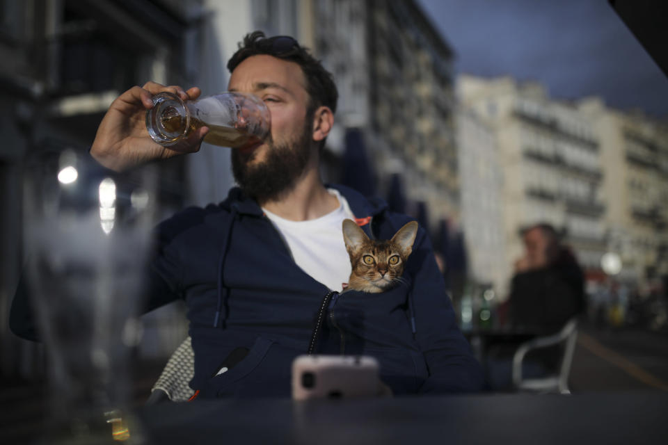 Naguey drinks a final beer with his cat Nela before bars and restaurants close, in Marseille, southern France, Sunday Sept. 27, 2020. As restaurants and bars in Marseille prepared Sunday to shut down for a week as part of scattered new French virus restrictions, Health Minister Olivier Veran insisted that the country plans no fresh lockdowns. (AP Photo/Daniel Cole)