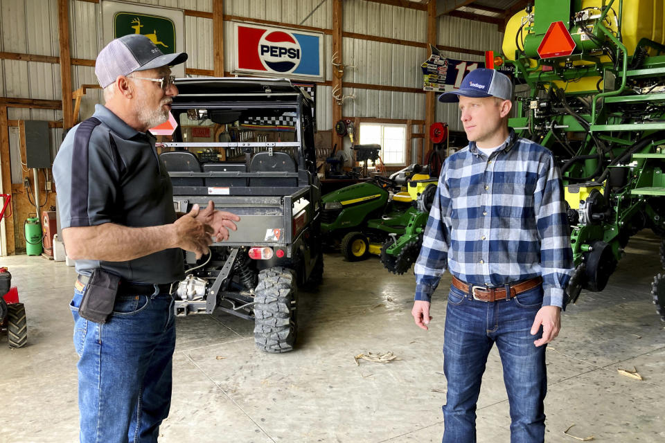 Farmer Rick Clifton, left, talks with Bryan Randall, an agronomist with Indigo Agriculture in Orient, Ohio, on April 5, 2021. Indigo pays Clifton and other producers to use techniques that keep carbon in the soil instead of releasing it to the atmosphere. Clifton grows cereal rye and rapeseed as off-season cover crops and uses no-till cultivation. (AP Photo/John Flesher)