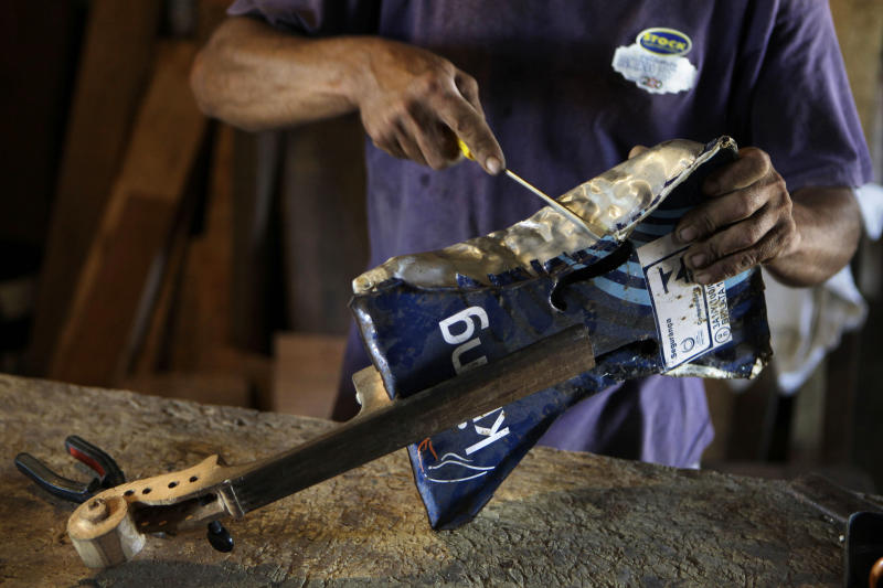 "In this Dec. 11, 2012 photo, Nicolas Gomez makes a violin with recycled materials at his home in the Cateura, a vast landfill outside Paraguay's capital of Asuncion, Paraguay. Gomez, a trash picker and former carpenter, was asked by Favio Chavez, the creator of ìThe Orchestra of Instruments Recycled From Cateura,"" to make instruments out of materials from the dump to help keep the younger kids occupied. ìI only studied until the fifth grade because I had to go work breaking rocks in the quarries,î said Gomez, 48. (AP Photo/Jorge Saenz)"