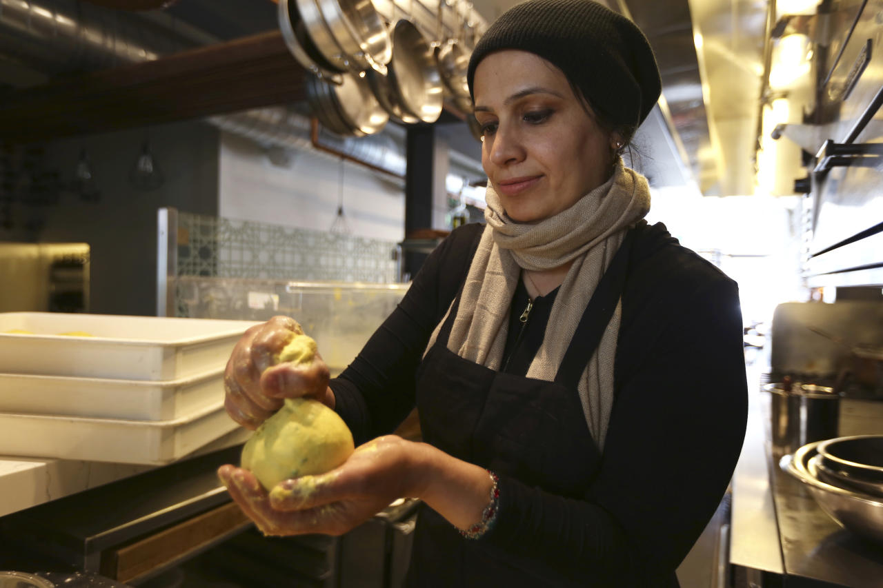 In this photo taken June 20, 2018, Muna Anaee, prepares a ball of khobz orouk, a flatbread she would eat frequently in her native Iraq, at the Tawla restaurant kitchen in San Francisco during the inaugural Refugee Food Festival. San Francisco restaurants are opening their kitchens for the first time to refugees who are showcasing their culinary skills and native cuisines while raising their profiles as aspiring chefs as part of a program to increase awareness about the plight of refugees worldwide. (AP Photo/Lorin Eleni Gill)