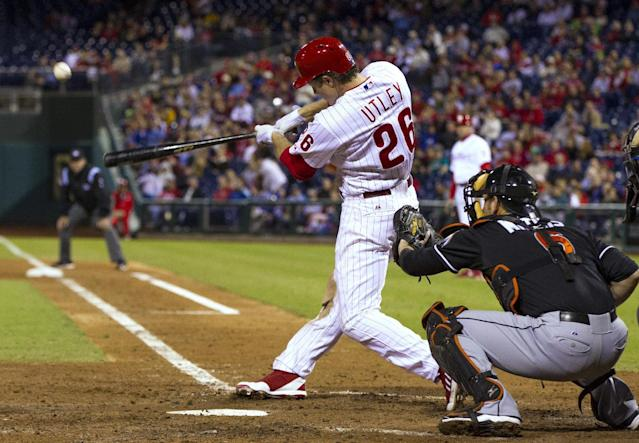 Philadelphia Phillies' Chase Utley, left, hits a three-run home run to right field as Miami Marlins catcher Jeff Mathis watches during the fifth inning of a baseball game, Tuesday, Sept. 17, 2013, in Philadelphia. (AP Photo/Chris Szagola)