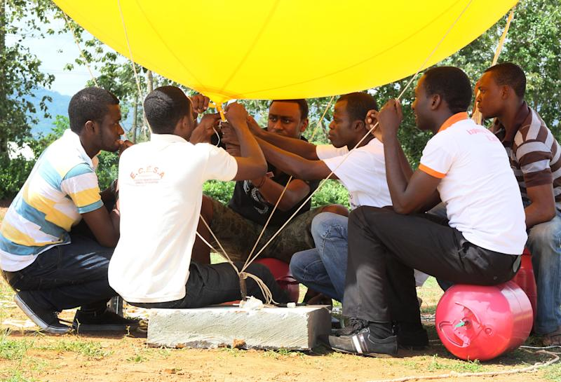 In this photo dated Tuesday, May 14, 2013, students prepare the balloon that will be used to conduct a test launch of a Coke-can sized satellite, at All Nations University in Koforidua, Ghana. Ghanaian college students plan Wednesday to launch a model of a satellite the size of a Coke can 200 yards (meters) into the air. Organizers hope that it will be the start of this West African country's space program.(AP Photo/Christian Thompson)
