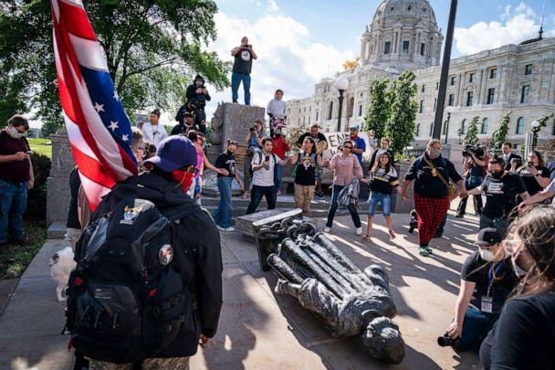 PHOTO: People dance in a circle around the Christopher Columbus statue after it was toppled in front of the Minnesota State Capitol in St. Paul, Minn., on June 10, 2020.  (Leila Navidi/Star Tribune via AP)