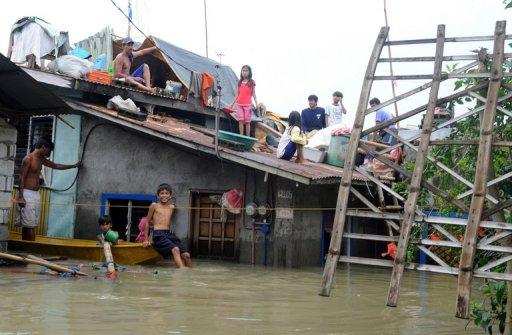 A family is seen being marooned on the roof of their home after floods swamped their village during the passage of Typhoon Nesat, in Pulilan, north of Manila, October 1. Massive flooding brought about by back-to-back typhoons could last for a month even as the storms' death toll reached 95, according to country's civil defence chief