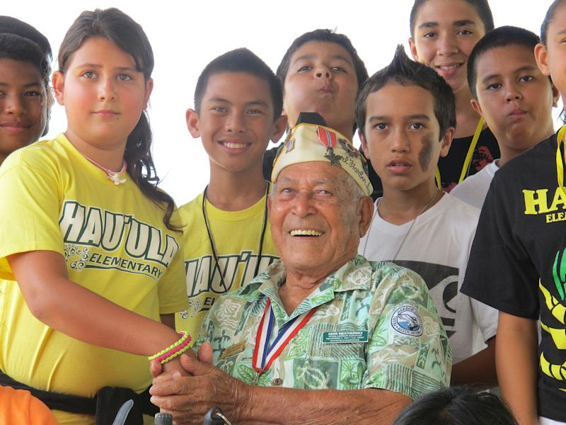 In this photo taken Nov. 22, 2013, Herb Weatherwax, seated, poses for a photo with Hauula Elementary School sixth graders from left Dawson Langinbelik, Rachel Cheney, Frank Kojima, La'a Beatty, Chase Colleado, Makoa Ahquin-Soren and Keola Baily in Pearl Harbor, Hawaii. The 96-year-old retired electrician is one of four Pearl Harbor survivors who volunteers to greet visitors at the historic site. On Saturday is the 72nd anniversary of the 1941 attack by Japan on Pearl Harbor. (AP Photo/Audrey McAvoy)