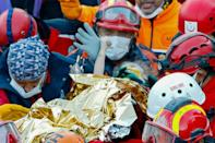Elif Perincek, 3, holds the thumb of her rescuer after she was found in the rubble of a building collapsed by an earthquake in Turkey
