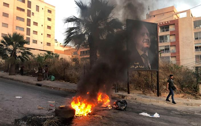 A man walks near a burning fire blocking a road during a protest against mounting economic hardships in Beirut last mont - Issam Abdallah/Reuters