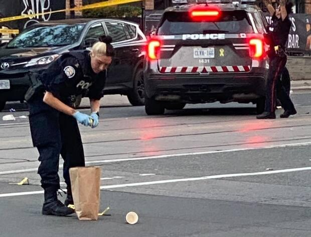 A Toronto police officer collects bullet shells at Bathurst Street and Stewart Street on Aug. 27, 2021. (Martin Trainor - image credit)
