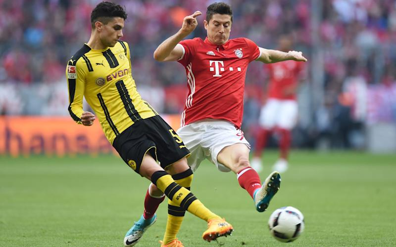 Dortmund's Spanish defender Marc Bartra (L) and Bayern Munich's Polish forward Robert Lewandowski vie for the ball during the German first division Bundesliga football match FC Bayern Munich v BVB Borussia Dortmund in Munich, southern Germany, on April 8, 2017 - Credit: AFP
