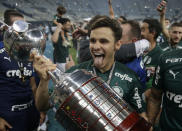 Raphael Veiga of Brazil's Palmeiras holds the trophy as he celebrates with teammates after winning the Copa Libertadores final soccer match against Brazil's Santos at the Maracana stadium in Rio de Janeiro, Brazil, Saturday, Jan. 30, 2021. Palmeiras won 1-0.(Ricardo Moraes/Pool via AP)