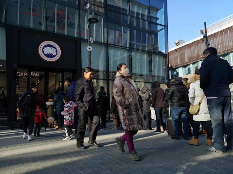 BEIJING, CHINA - DECEMBER 30: People line up to enter a Canada Goose flagship store at Sanlitun on December 30, 2018 in Beijing, China. Canada Goose opened its first flagship store in Beijing on Sunday. (Photo by Visual China Group via Getty Images/Visual China Group via Getty Images)