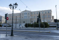 A woman walks in front of the Greek parliament during the first day of a lockdown, in Athens, Saturday, Nov. 7, 2020. With a surge in coronavirus cases straining health systems in many European countries, Greece has announced a three-week nationwide lockdown. (AP Photo/Yorgos Karahalis)