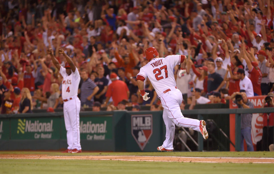 ANAHEIM, CA - JULY 17: First base coach Alfredo Griffin #4 and Mike Trout #27 of the Los Angeles Angels of Anaheim celebrate after Trout hit a walk-off home run in the bottom of the ninth inning to defeat the Boston Red Sox 1-0 at Angel Stadium of Anaheim on July 17, 2015 in Anaheim, California. (Photo by Matt Brown/Angels Baseball LP/Getty Images)