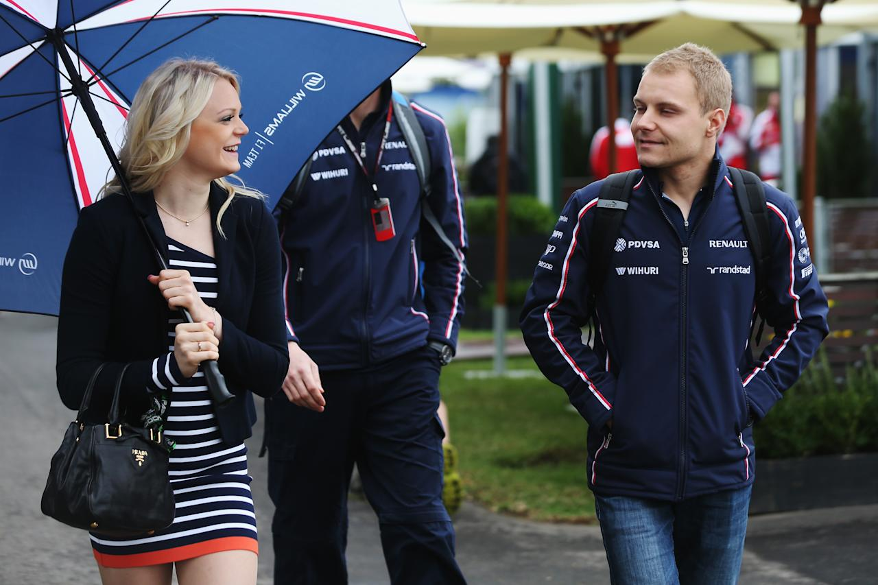 MELBOURNE, AUSTRALIA - MARCH 17:  Valtteri Bottas of Finland and Williams and his girlfriend Emilia Pikkarainen arrive in the paddock before the weather delayed qualifying session for the Australian Formula One Grand Prix at the Albert Park Circuit on March 17, 2013 in Melbourne, Australia.  (Photo by Mark Thompson/Getty Images)