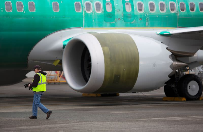 An employee walks past a Boeing 737 Max aircraft at Boeing's 737 Max production facility in Renton