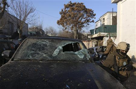 Afghan security forces walk near a damaged vehicle outside a Lebanese restaurant, the site of a suicide attack, in Kabul