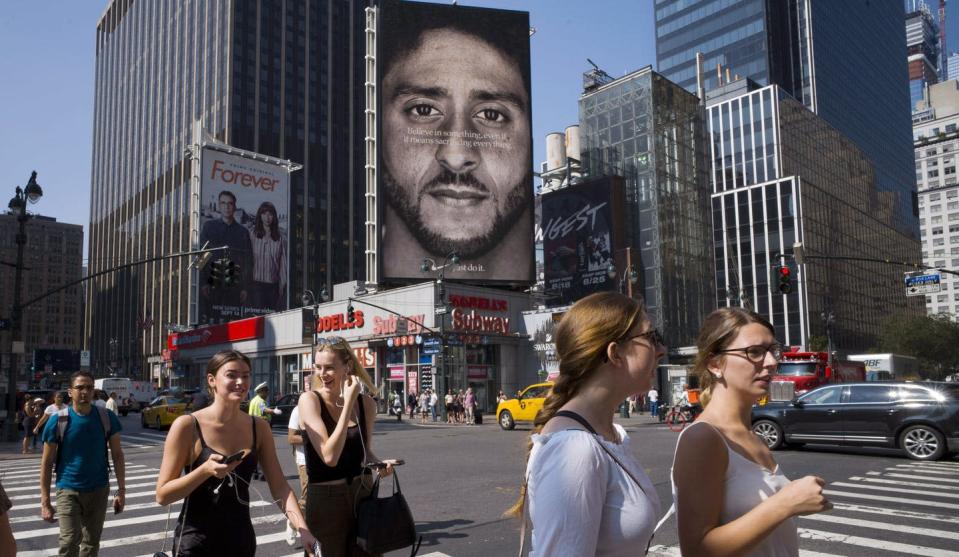 """<span class=""""caption"""">Nike ad in New York in 2018, showing former San Francisco 49ers quarterback Colin Kaepernick after his 2016 kneeling protest. Could a corporation sell an act like Kaepernick's 'kneel' as an NFT? </span> <span class=""""attribution""""><span class=""""source"""">(AP Photo/Mark Lennihan)</span></span>"""