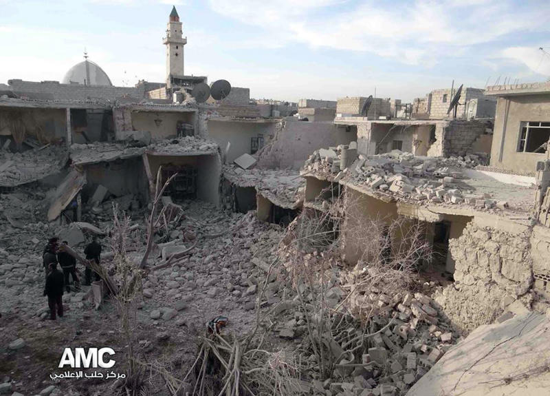 This citizen journalism image provided by Aleppo Media Center, AMC, which has been authenticated based on its contents and other AP reporting, Syrian citizens stand on rubble of houses that were destroyed due to Syrian forces airstrikes in Aleppo, Syria, Wednesday, Dec. 18, 2013. Syrian government aircraft dumped barrels packed with explosives on at least four opposition-held neighborhoods of Aleppo on Wednesday, the fourth day of stepped-up airstrikes on the contested northern city, activists said. (AP Photo/Aleppo Media Center AMC)