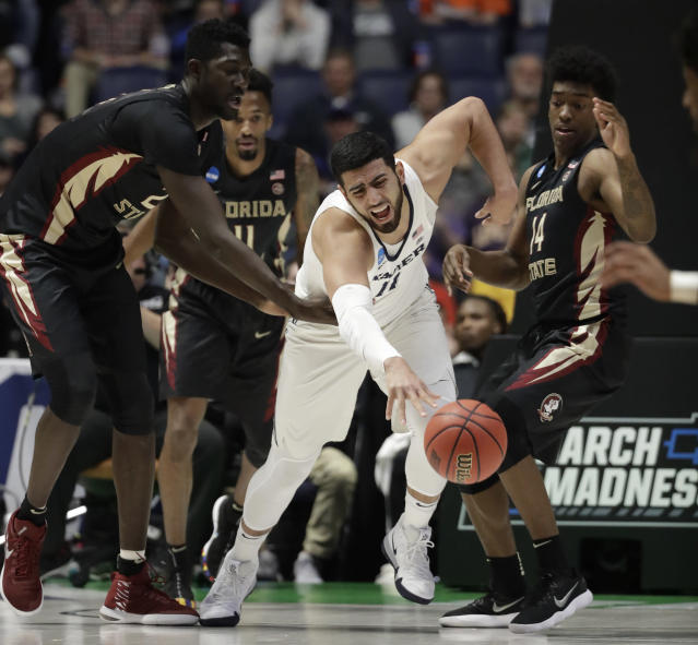 Xavier forward Kerem Kanter (11), center, goes around Florida State center Christ Koumadje (21) and guard Terance Mann (14), during the first half of a second-round game in the NCAA college basketball tournament in Nashville, Tenn., Sunday, March 18, 2018. (AP Photo/Mark Humphrey)